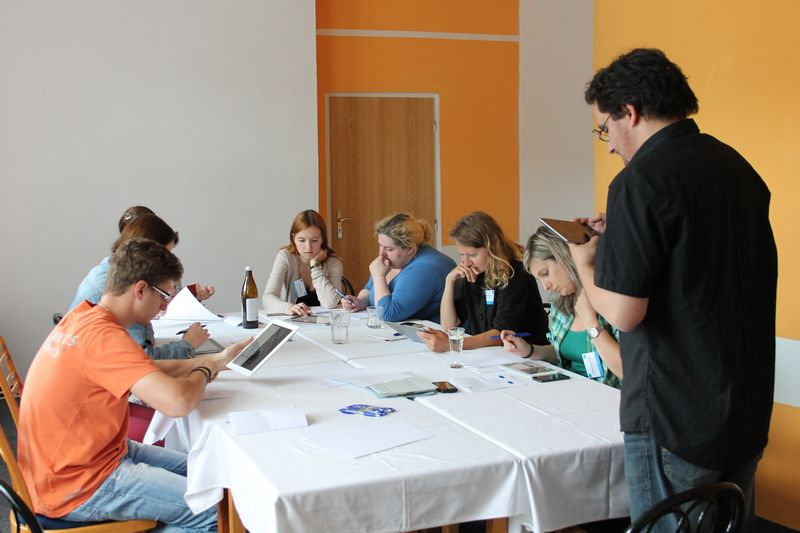 účastníci workshopu pod vedením mentora pracují s dotykovým tabletem